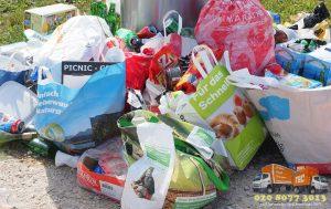 Waste pile next to a bin